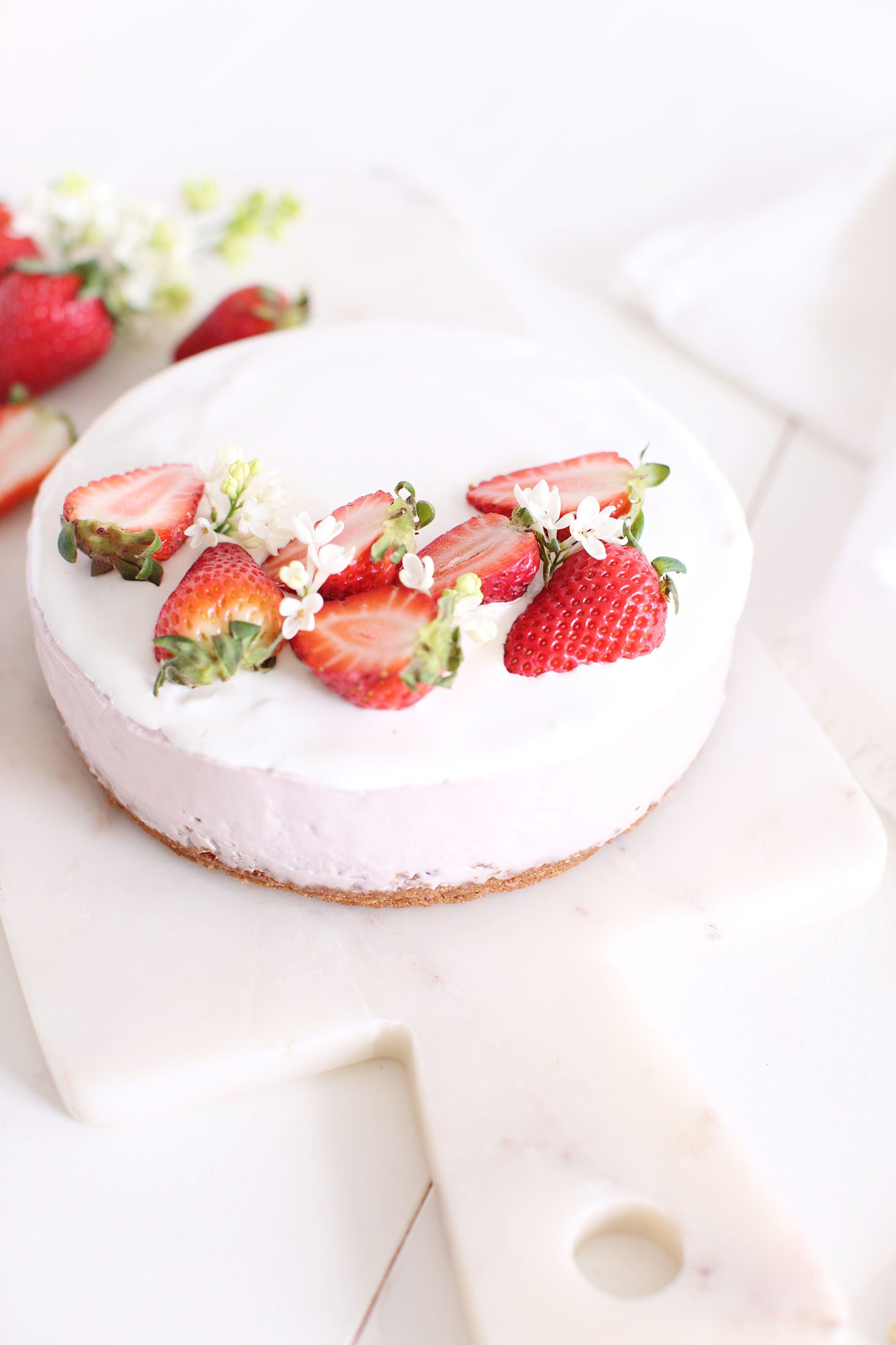 Vegan dessert, Cheesecake decorated with strawberries and small white flowers.
