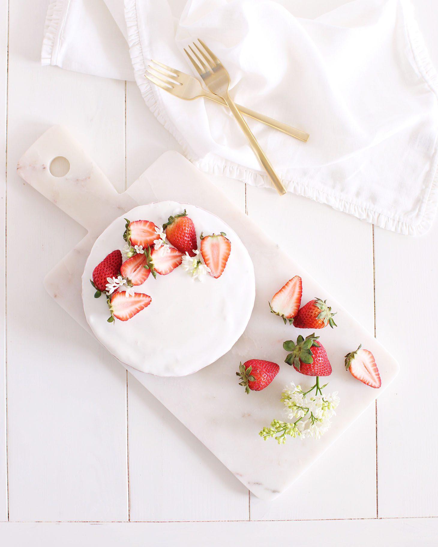 Jillian Harris Vegan Coconut Strawberry Cheesecake on marble cutting board with cut up strawberries.
