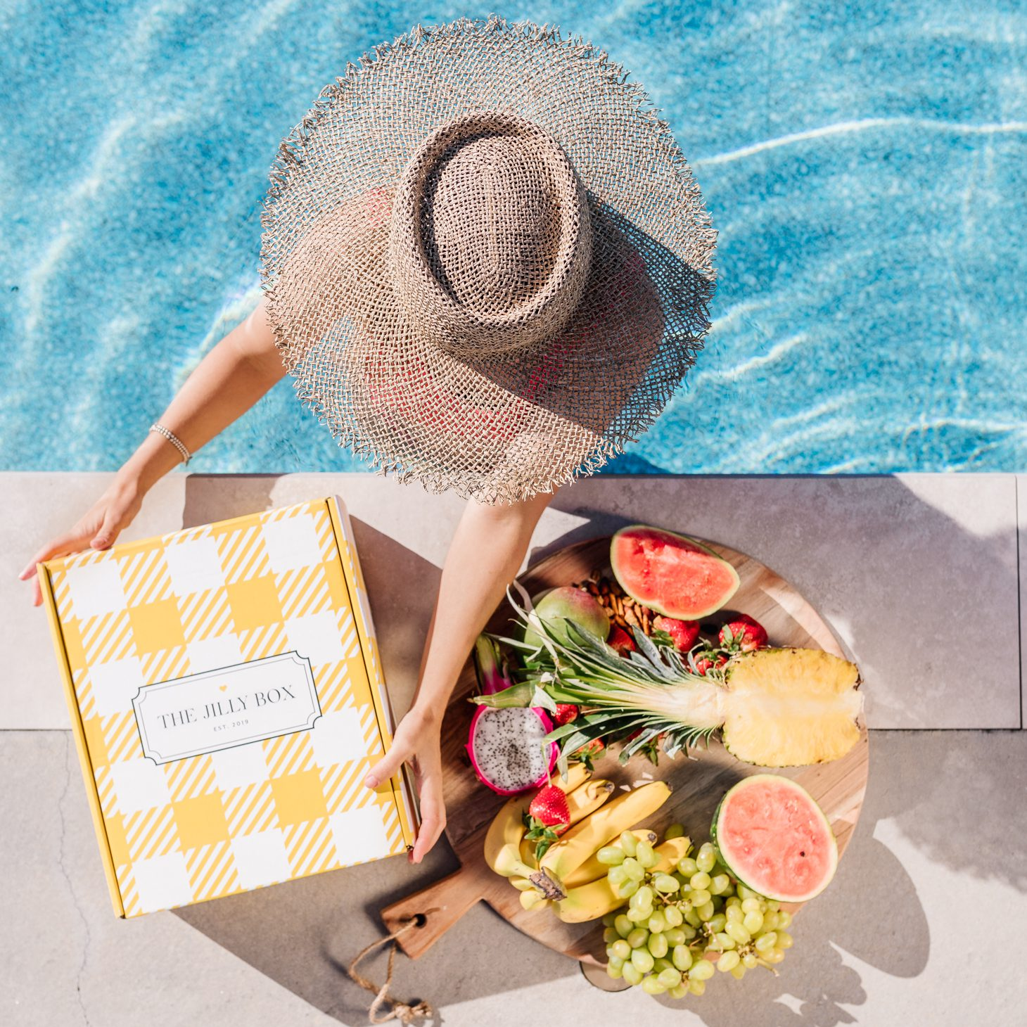 Jillian Harris in pool with fruit platter and the Summer 2020 Jilly Box