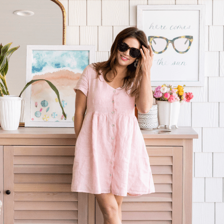 Jillian Harris wearing a pink dress and sunglasses while showcasing items available in her online shop.