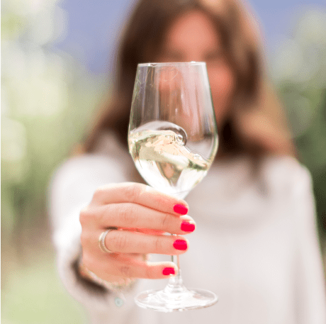 Jillian Harris Holding up a glass of white wine.