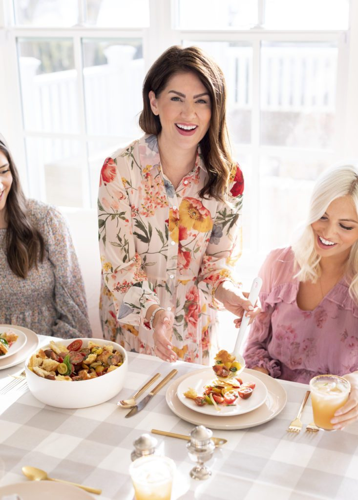 Jillian Harris standing at a table, smiling while she puts vegetables on Shay Merritt's plate.