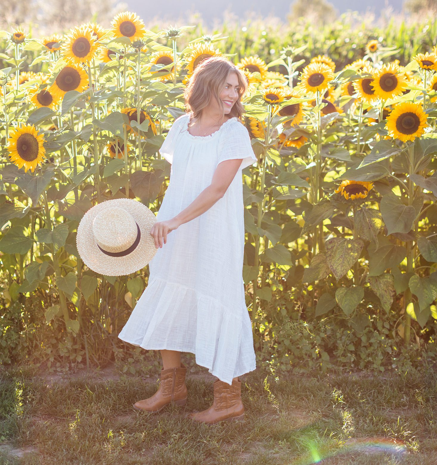 Jillian Harris in a White Dress with a Field of Sunflowers behind her
