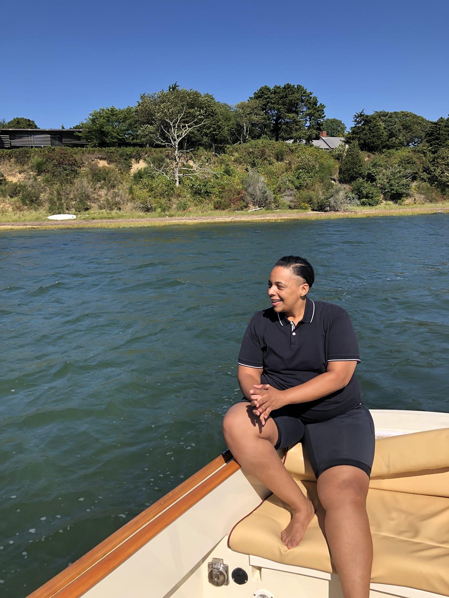Health and Wellness coach, Coach Carey on a boat on a lake.
