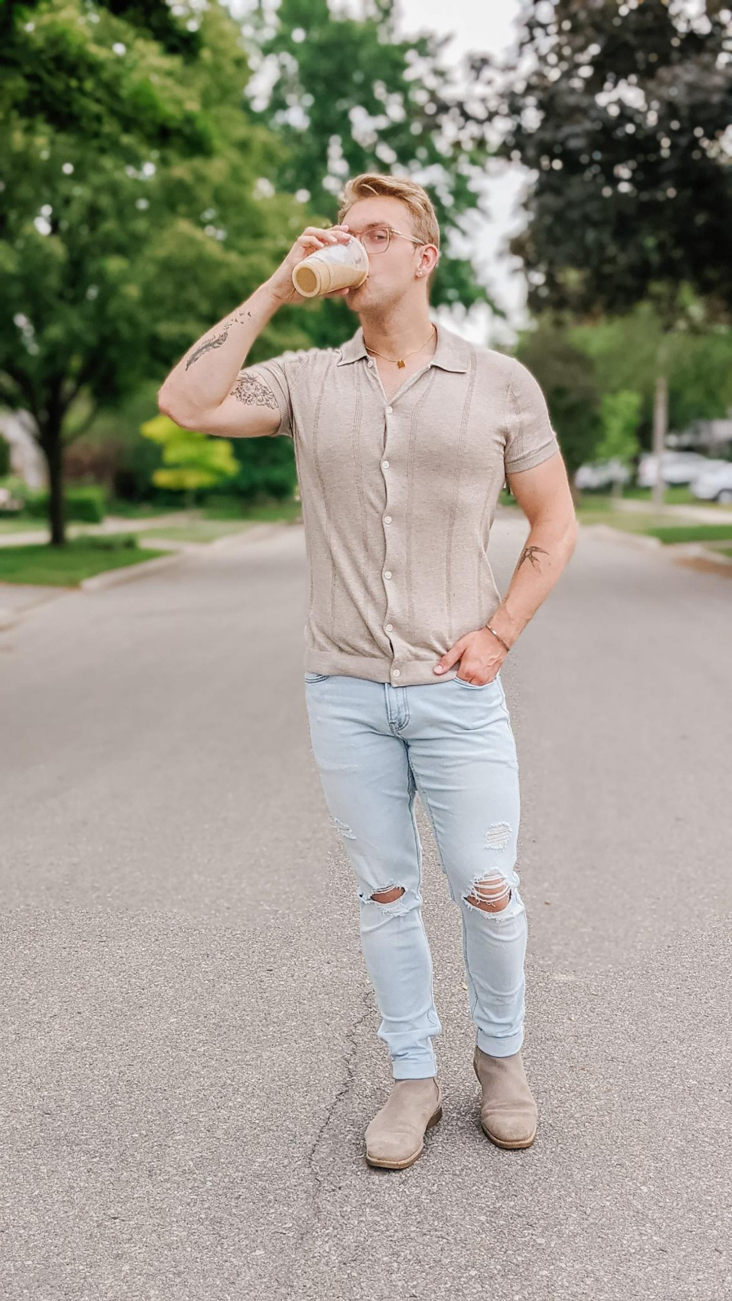 Christoper Allen standing in the middle of a residential street lined with trees, drinking coffee while showing one of his Favourite Summer Looks.