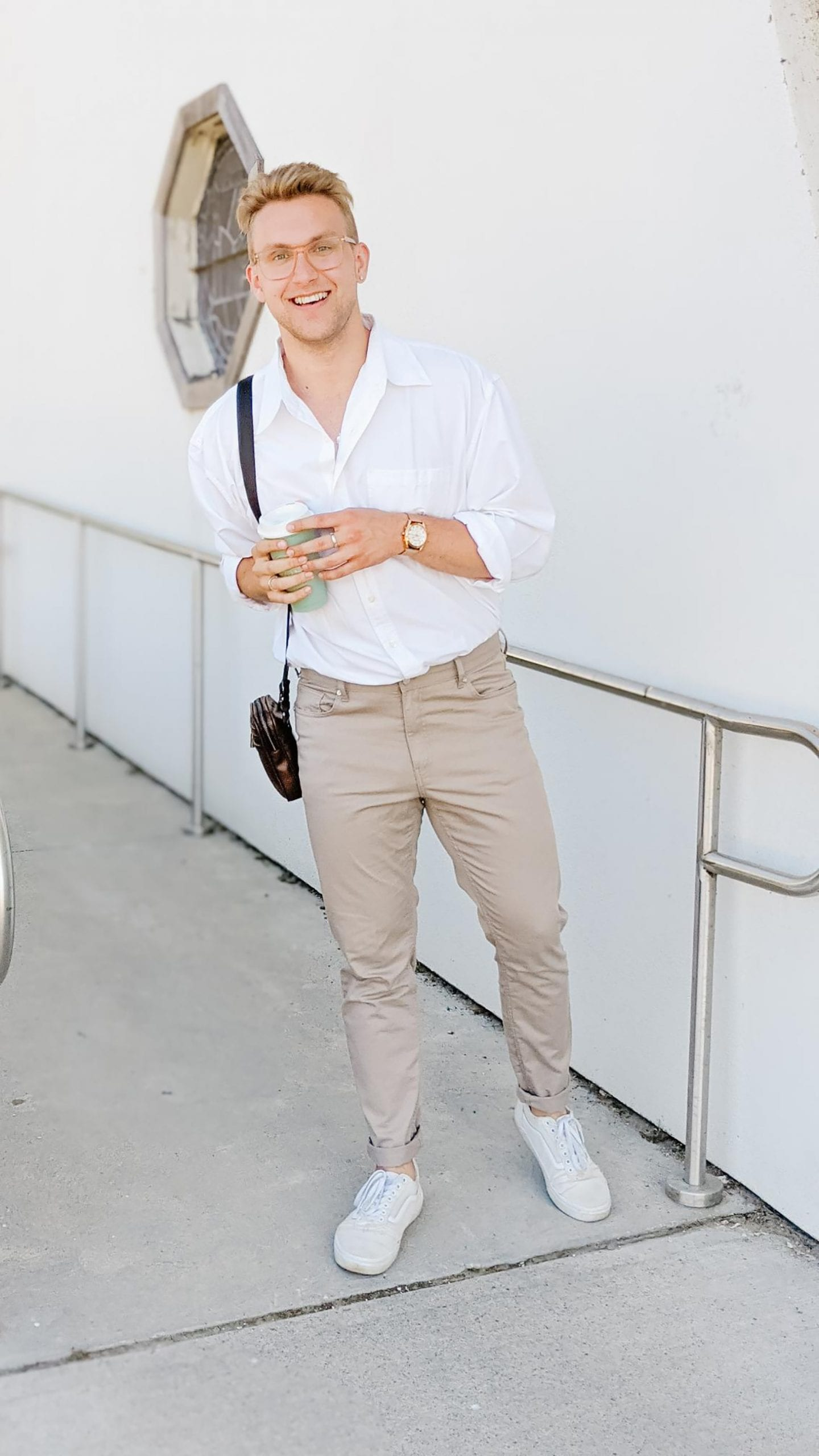 Blonde man, Christoper Allen, standing outside of a white building wearing a casual white button down shirt and tapered khaki pants.