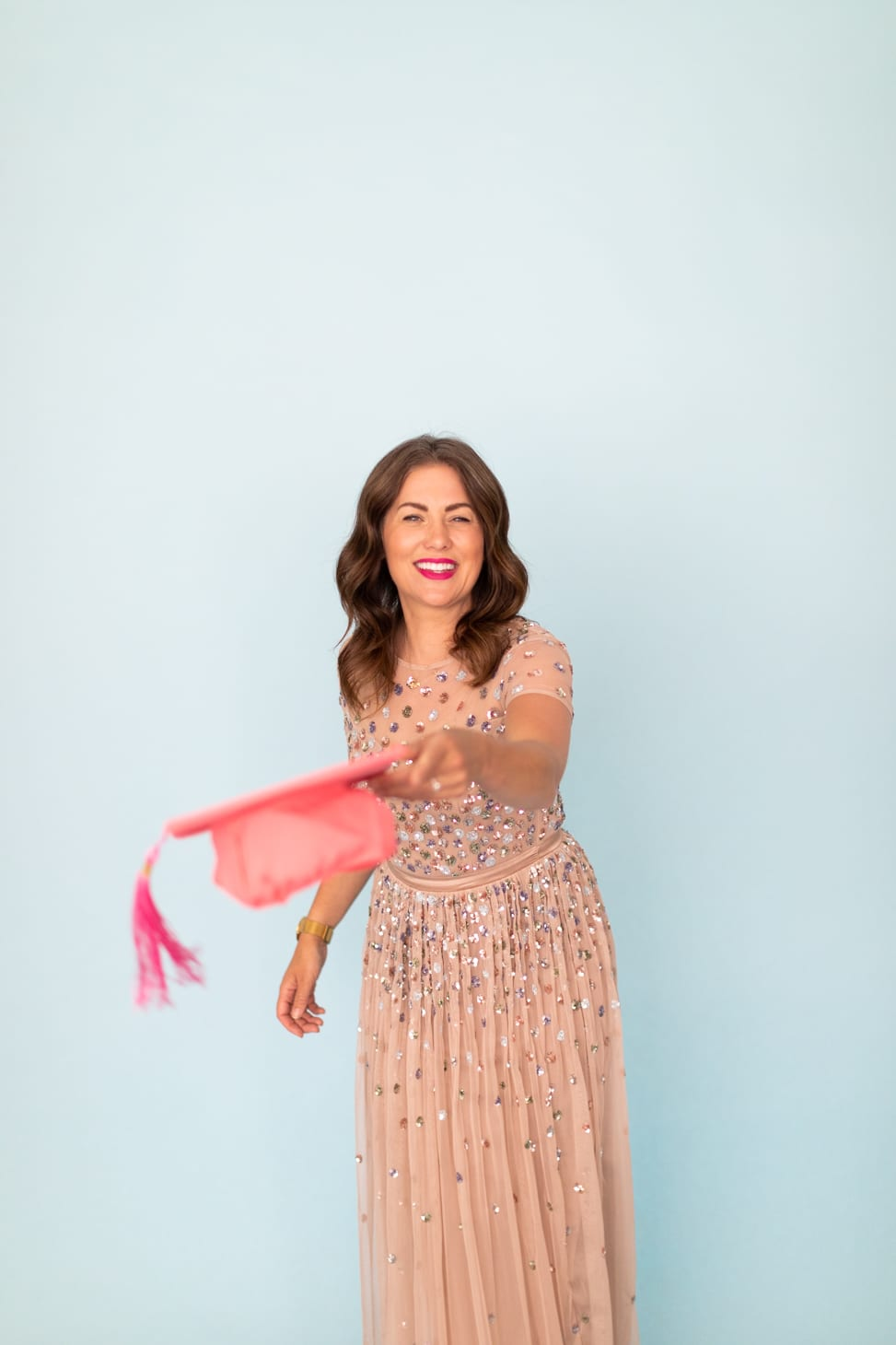 Jillian Harris for The Jilly Academy throwing a graduation cap in the air for the Alumni members.