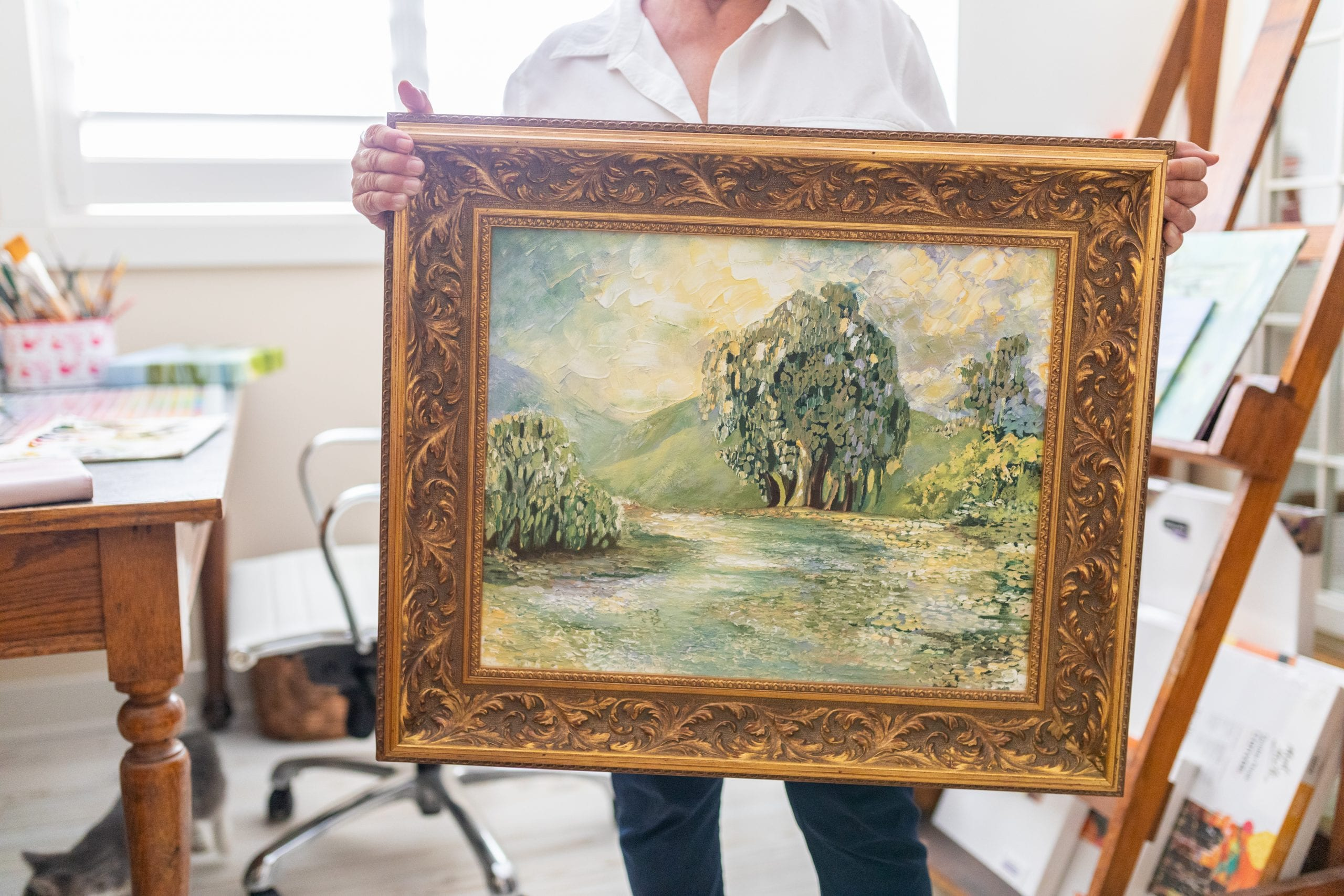 Peggy Harris holding a framed painting of an outdoor scene with trees, a field and a rolling green hill in the background.
