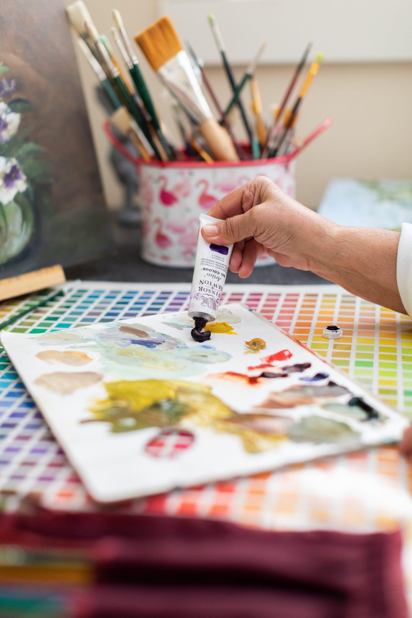 Peggy Harris applying dark purple oil paint to her painting palette.