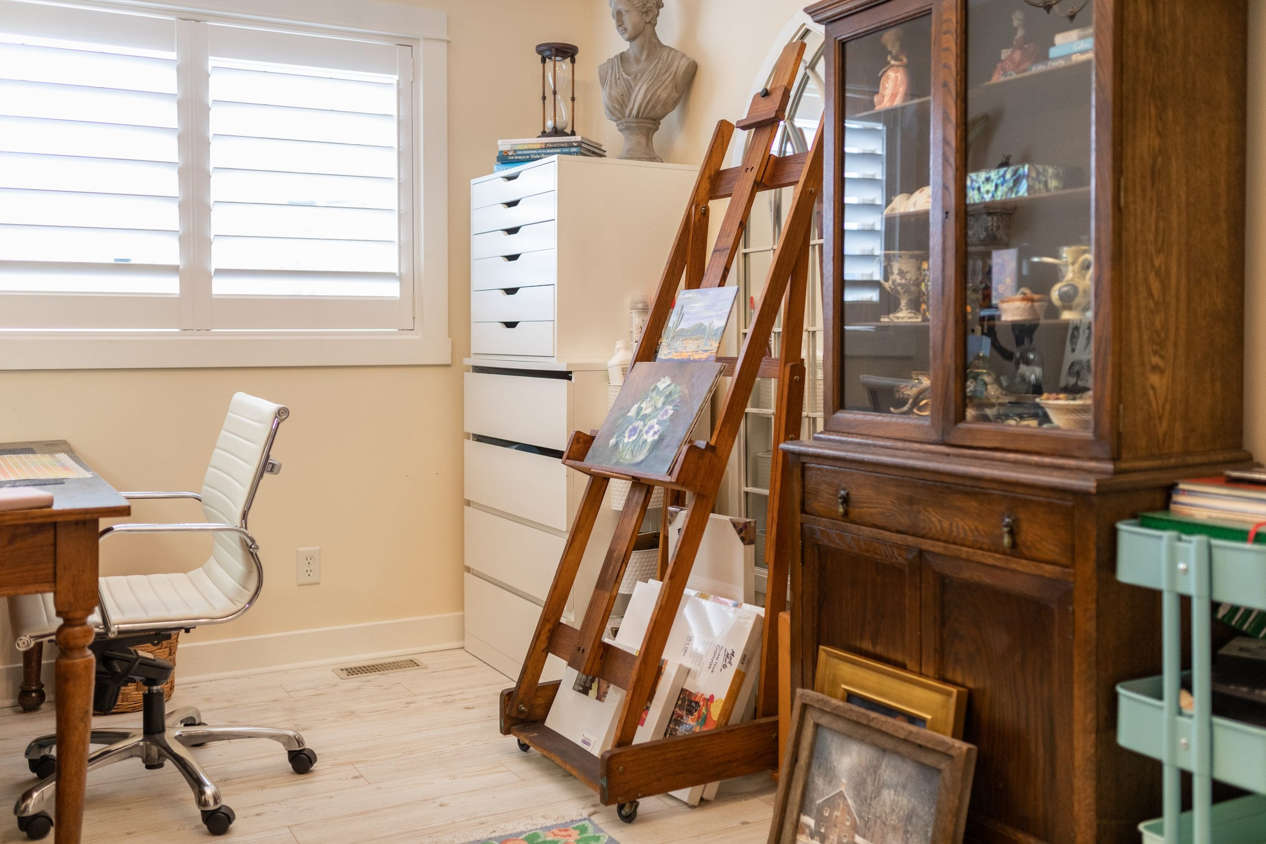 Peggy, Jillian Harris' mother's easel set up in her office with a painting of flowers on the easel.