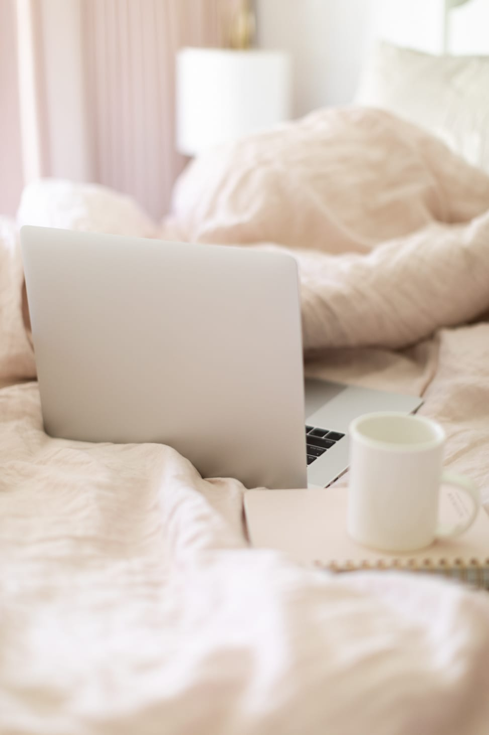 Jillian Harris' laptop and coffee in her bed working on The Jilly Academy in the summer.