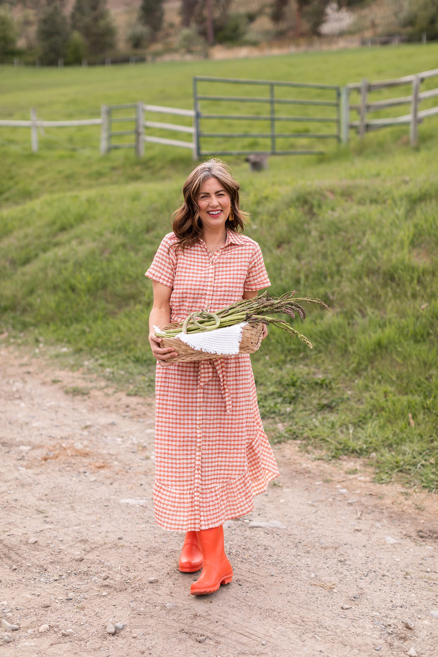 Jillian Harris wearing orange gingham printed dress and orange gum boots while carrying a basket of asparagus, showing one of her farm-inspired outfits.