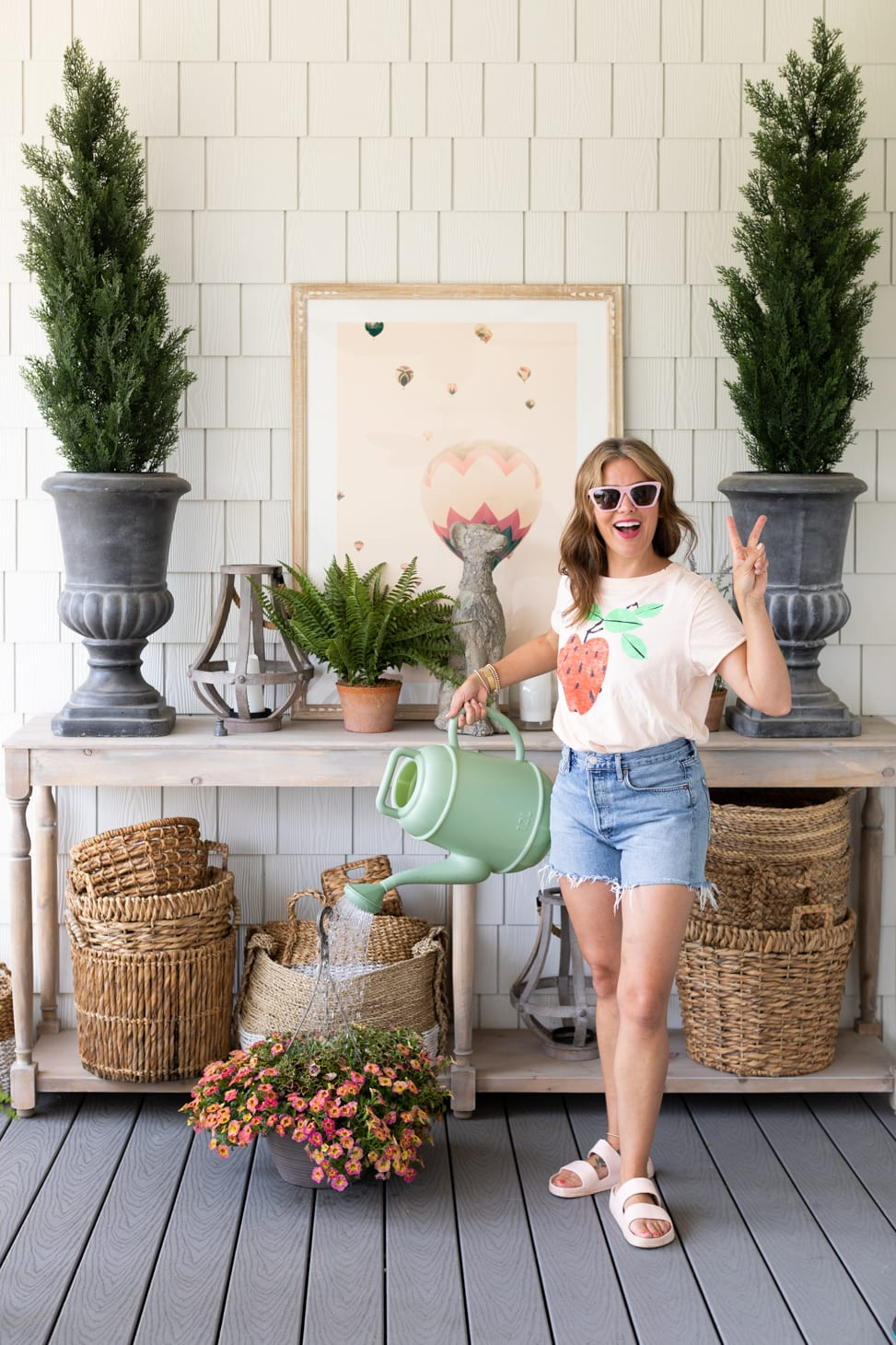 Jillian Harris watering a hanging basket of flowers on her porch wearing one of her Go-To Farm-Inspired Outfits.