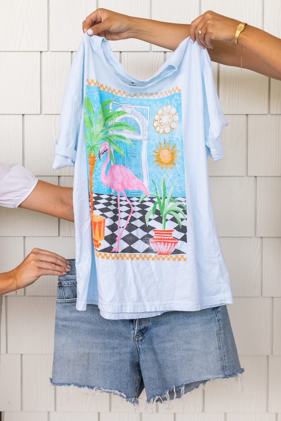 Jillian Harris' Farm-Inspired styled outfit showing a white t-shirt with a flamingo and tropical plants on it paired with distressed cut-off denim shorts.