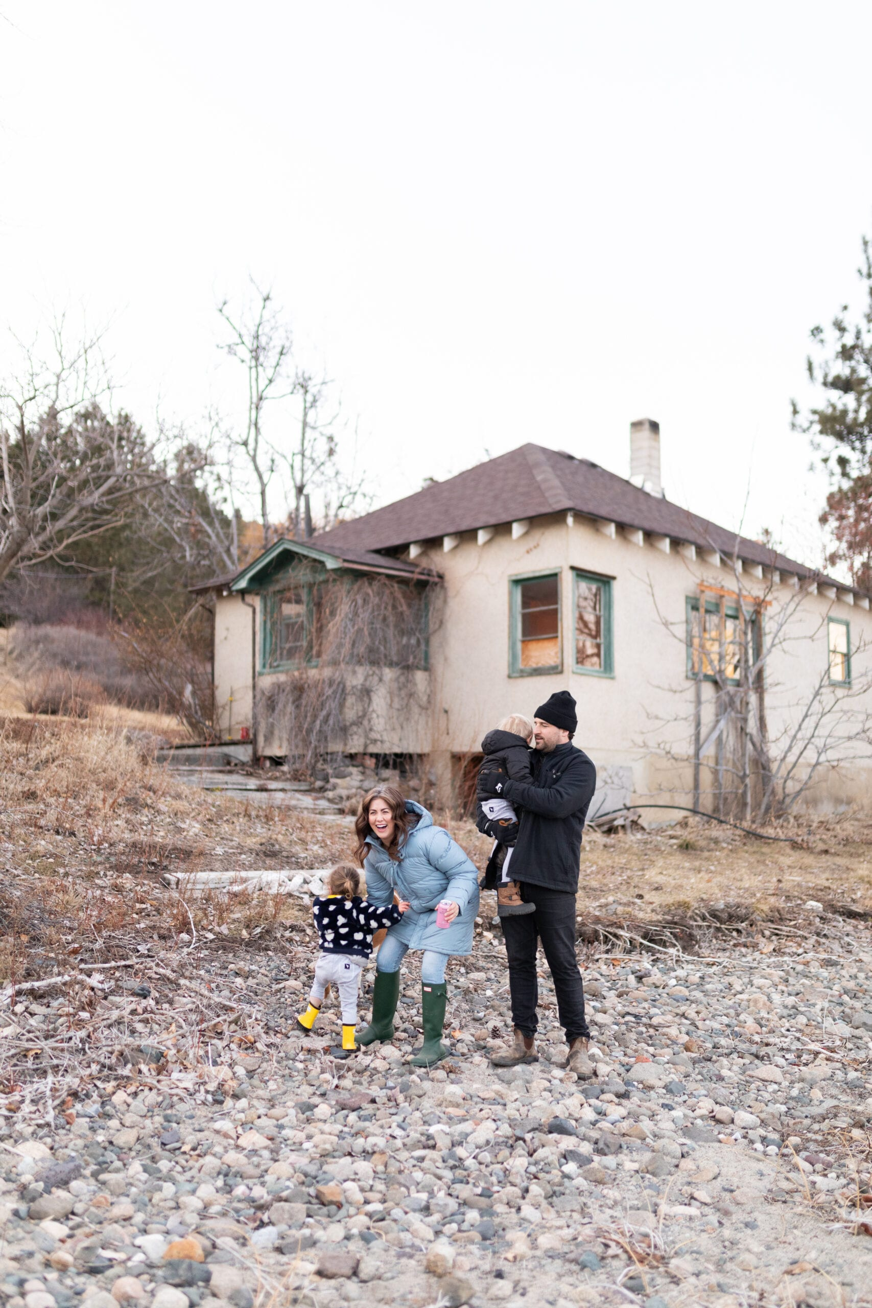 Jillian, Justin and their children out in front of the farmhouse before renovations.