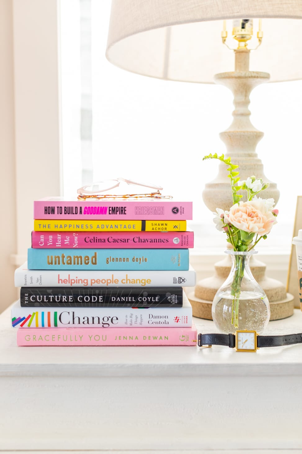 Jillian Harris's nightstand with a stack of books that encourages growth along with a lamp, flowers in a vase and watch.