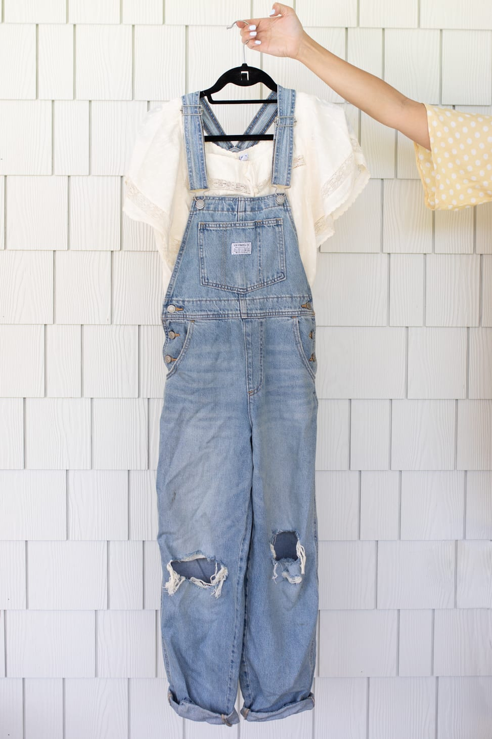Light denim overalls with holes in knee area paired with a short sleeved white peasant shirt, an example of Jillian Harris' Favourite Farm-Inspired Looks.