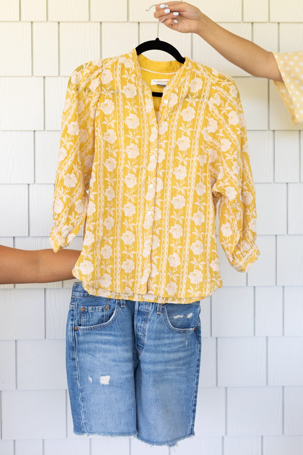 An outfit with yellow and white floral patterned button down shirt with Agolde mid-thigh cut-off denim shorts, one of her farm-inspired outfits.