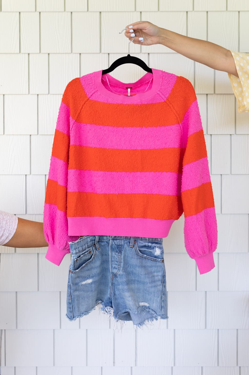 Jillian Harris' New Favourite Denim Shorts shown paired with with a light sweater with pink and red horizontal stripes.