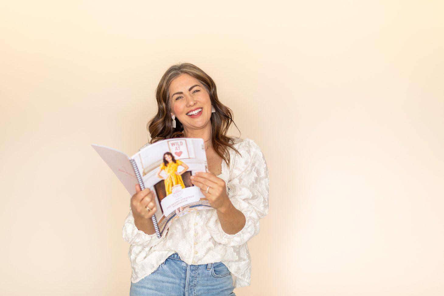 Jillian Harris on a plain backdrop with a Jilly Academy workbook ready for fall semester.