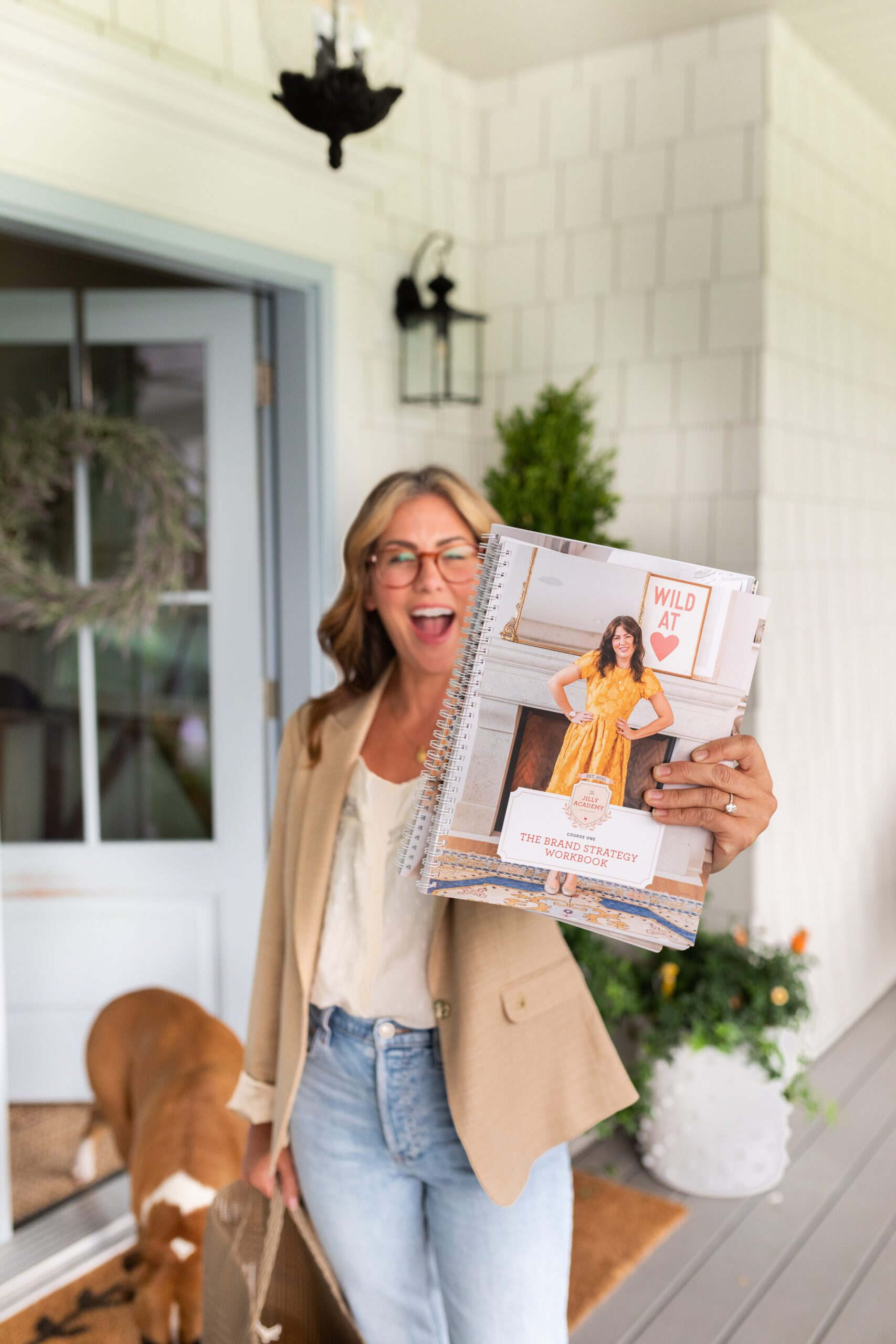 Jillian Harris on her front porch showing excitement for The Jilly Academy's Fall Semester, holding the workbook.