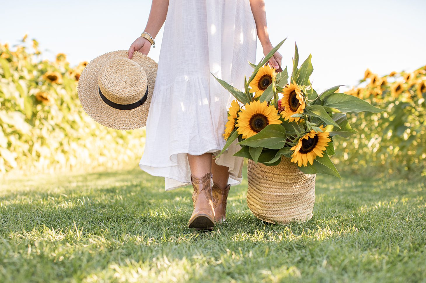 Jillian Harris with a basket of sunflowers and sunhat, a photo that is part of The Campus Store stock photo collections the Alumni love.